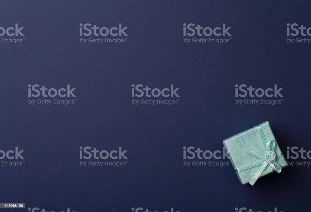 small gift box on dark blue paper background stock photo