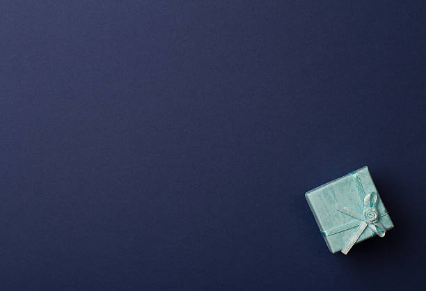 small gift box on dark blue paper background - flyer inspiration stock-fotos und bilder