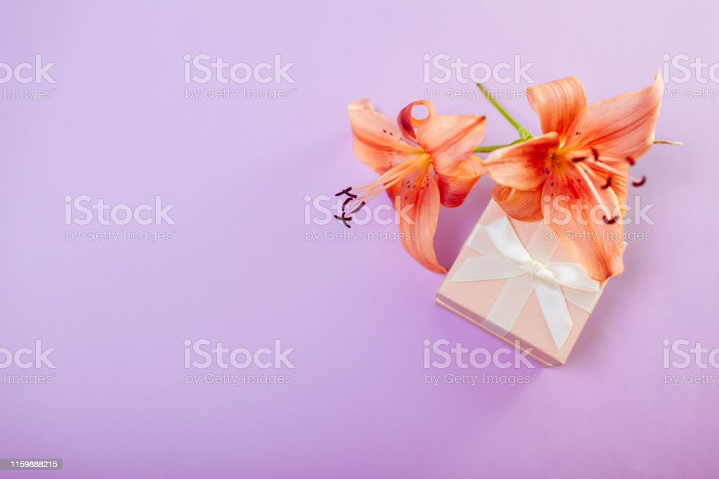 Small gift box with with ribbon surrounded with flowers. Jewellery as...