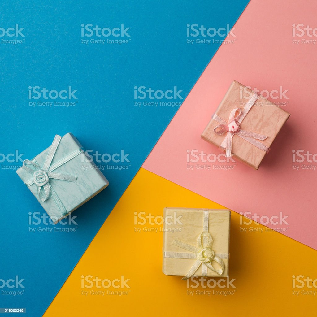small gift boxes on multicolored paper background stock photo