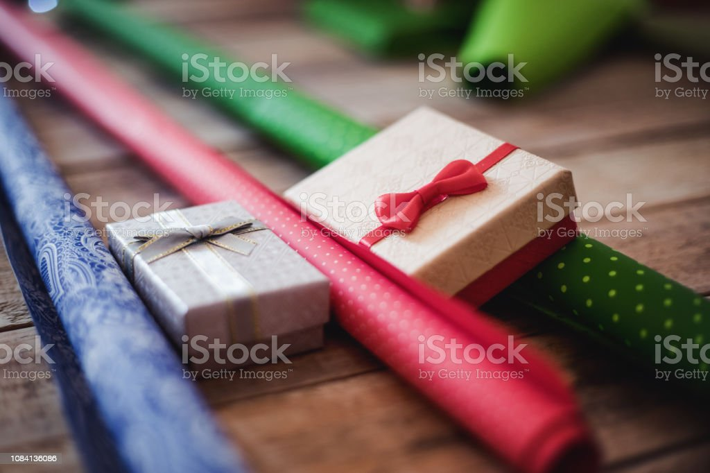 Small gift boxes and wrapping paper rolls at table, ready for...