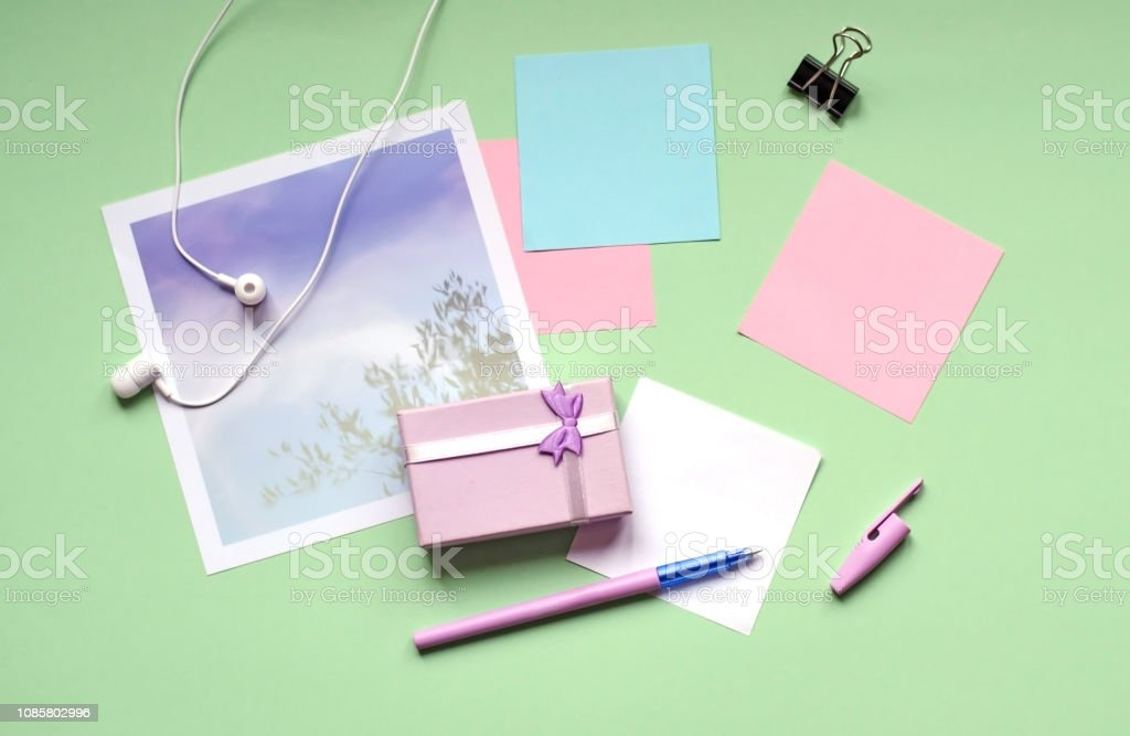 A small gift of pale lilac. Office, stickers, pen on a green...