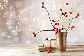 small gift parcels and rosehip branches on a rustic wooden table against a vintage wall with blurred bokeh lights, autumn or christmas decoration with copy space