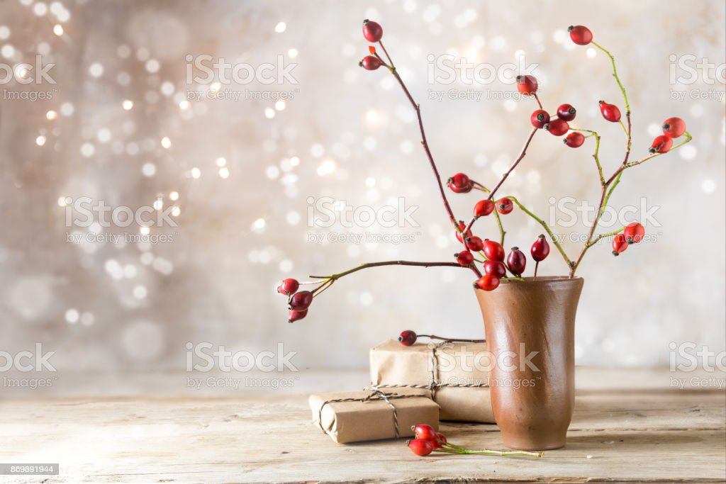 small gift parcels and rosehip branches on a rustic wooden table against a vintage wall with blurred bokeh lights, autumn or christmas decoration with copy space stock photo