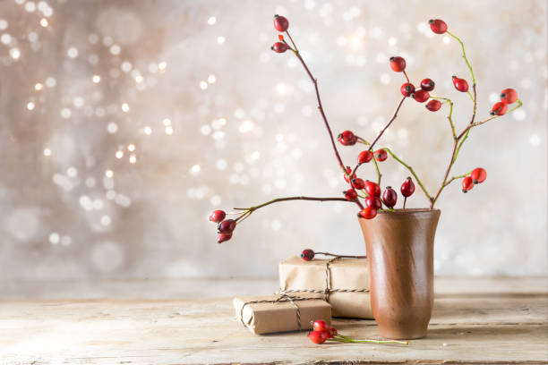 small gift parcels and rosehip branches on a rustic wooden table against a vintage wall with blurred bokeh lights, autumn or christmas decoration with copy space small gift parcels and rosehip branches on a rustic wooden table against a vintage wall with blurred bokeh lights, autumn or christmas decoration with copy space, selected focus religious celebration stock pictures, royalty-free photos & images