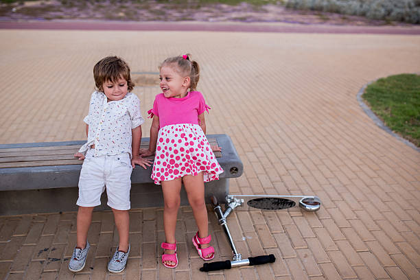 Kleine Mädchen und Jungen, die zusammen auf einer Bank. – Foto