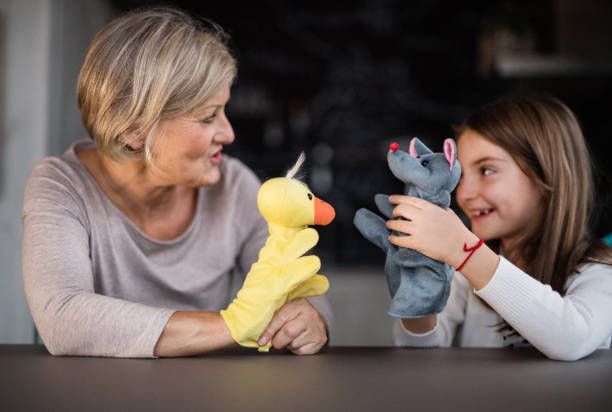 A small girl and grandmother playing at home. A small girl and her grandmother playing with hand puppets at home. Family and generations concept. puppet stock pictures, royalty-free photos & images