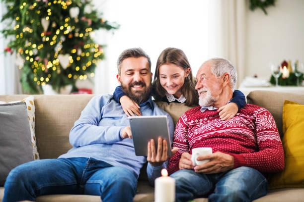 klein meisje en haar vader en grootvader zittend op een bank met kerstmis, met behulp van tablet pc. - family winter holiday stockfoto's en -beelden