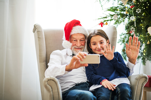 A small girl and her grandfather with Santa hat taking selfie with smartphone at Christmas time.
