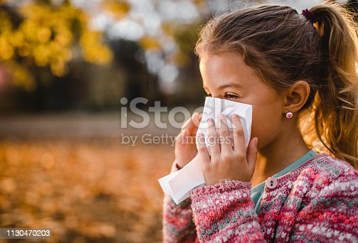 Ill little girl blowing a nose in autumn day at the park. Copy space.