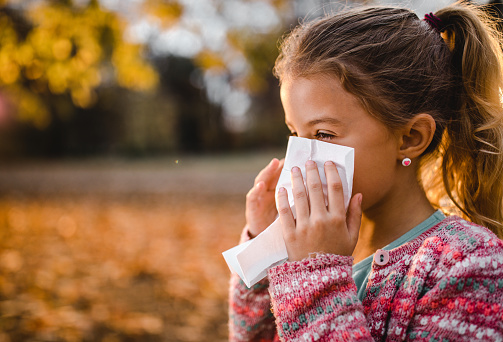 istock Small girl blowing her nose into a napkin outdoors. 1130470203
