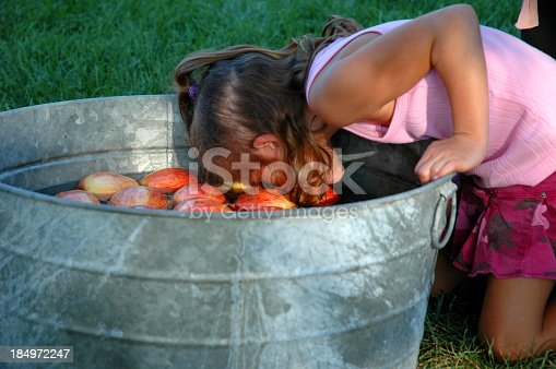 Little girl bobbing for apples at her birthday party
