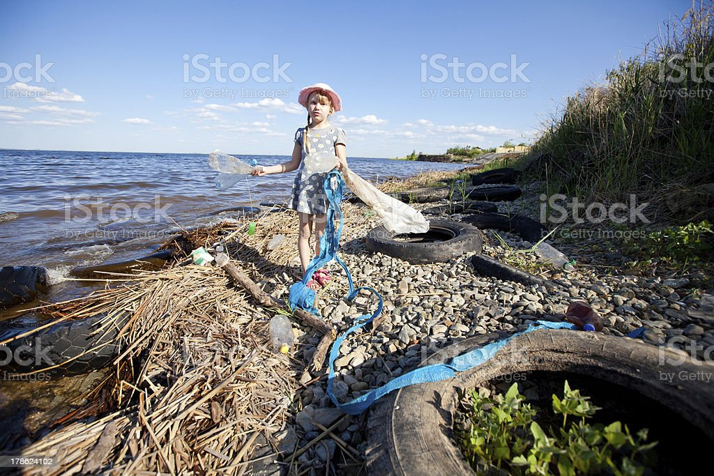 small girl collecting rubbish stock photo