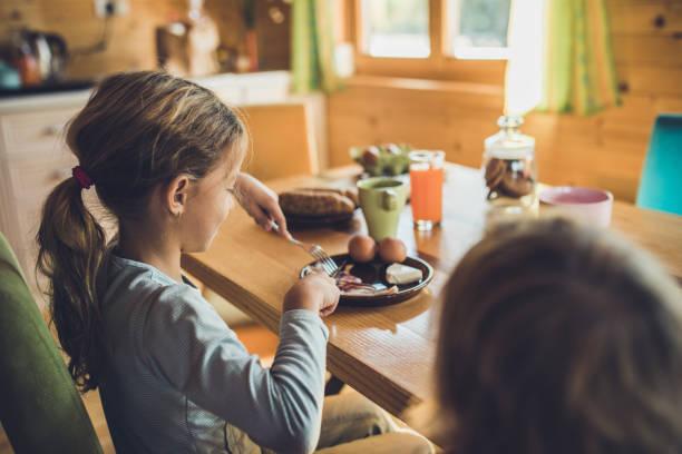 liten flicka skär bacon under hennes frukost hemma. - bordsskick bildbanksfoton och bilder