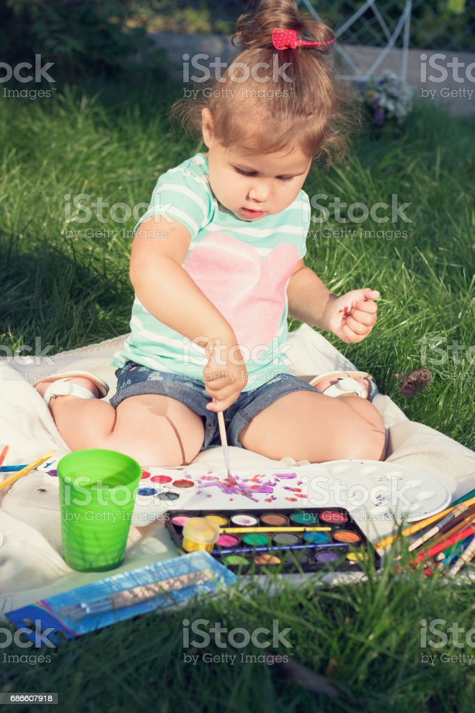 Small girl draws by the brush colorful paintings royalty-free stock photo