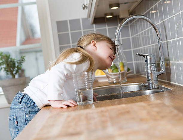 small girl drinking water - drinking water stock photos and pictures