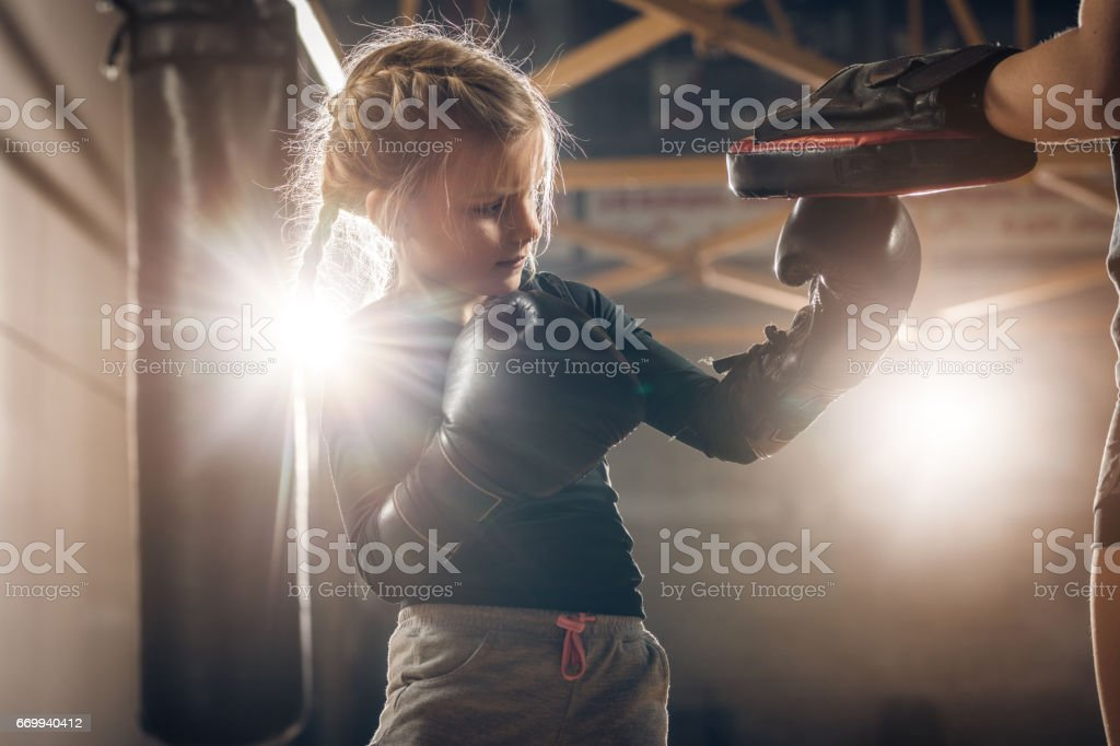 Small girl exercising boxing with unrecognizable coach in a health club. stock photo