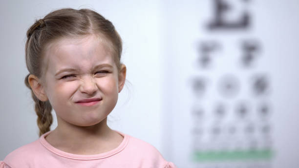 Small girl frowning, trying to see letter on vision testing table blurred vision stock photo