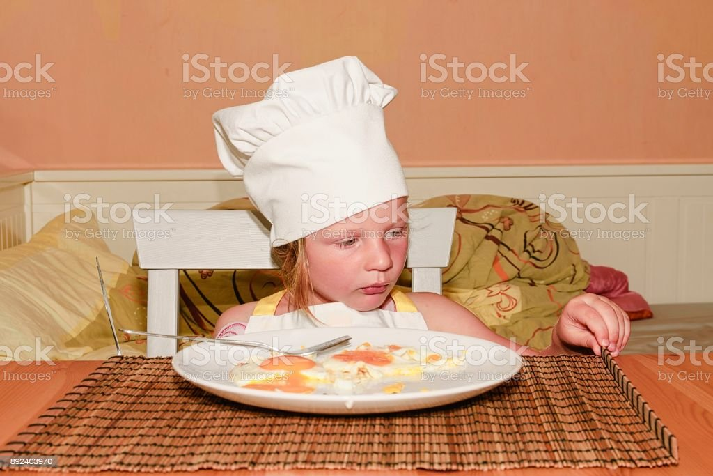 70b5ec832 Small girl has a snack. Little girl eats ham and eggs. Cute girl dressed  like a chef - white chef costume. Family and childhood concept. - Stock  image .