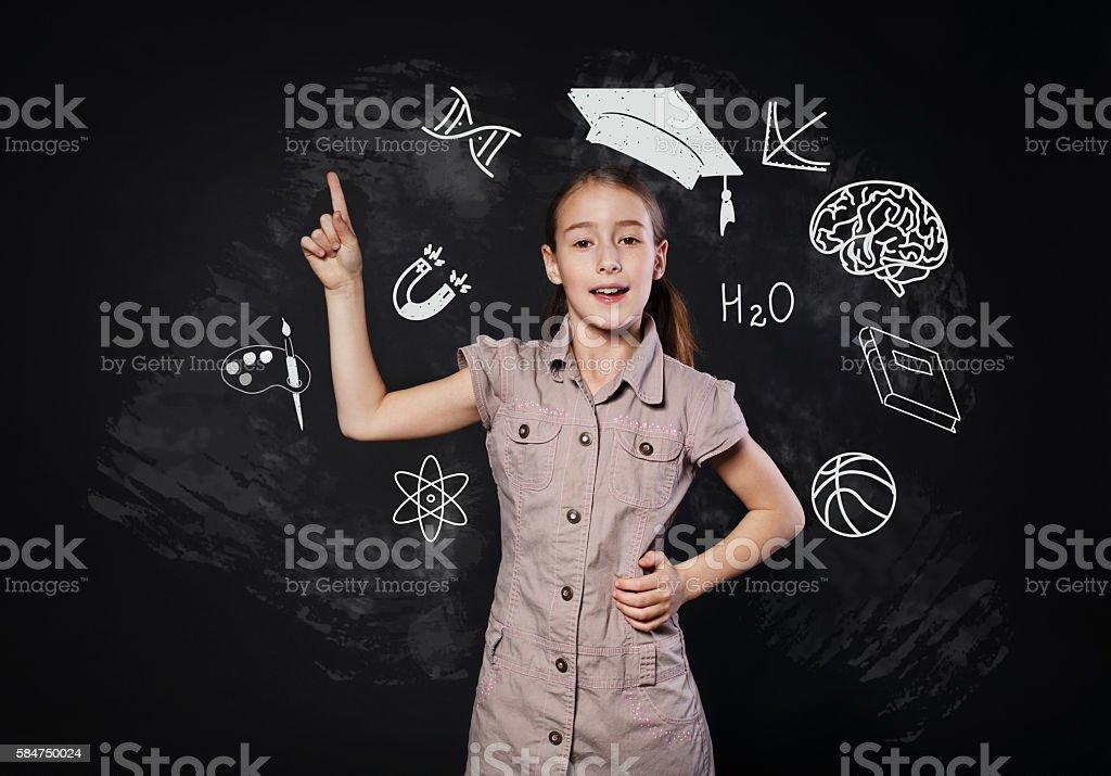 Small girl has idea near chalkboard. Child shows finger up stock photo