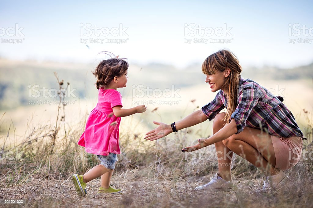 Small girl in nature running into mother's arms. Lizenzfreies stock-foto