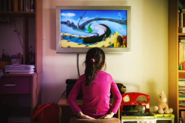 Small Girl is Watching a Cartoon Candid scene from ordinary life, small girl is watching cartoon on TV. cartoon and kids stock pictures, royalty-free photos & images