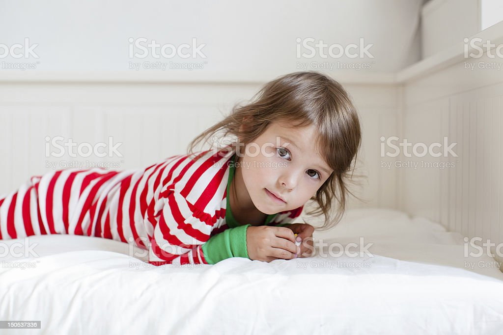 Small girl laying on her bad in striped pajamas royalty-free stock photo