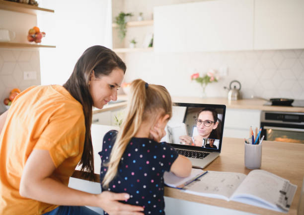 Small girl learning through internet indoors at home, Corona virus and quarantine concept. stock photo