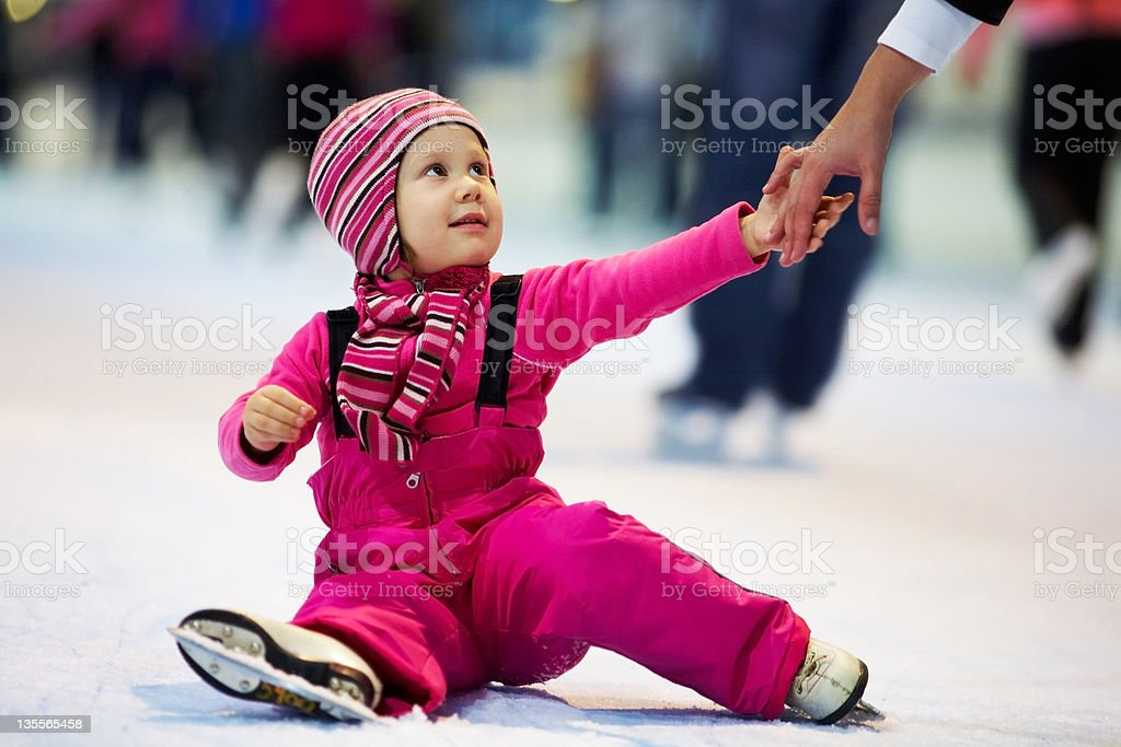 Small girl learning to ice skate stock photo