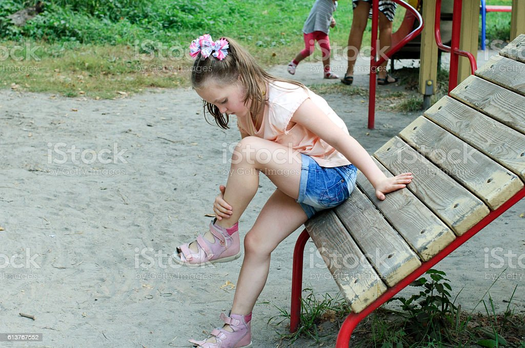 Small girl looks at her bruise – Foto