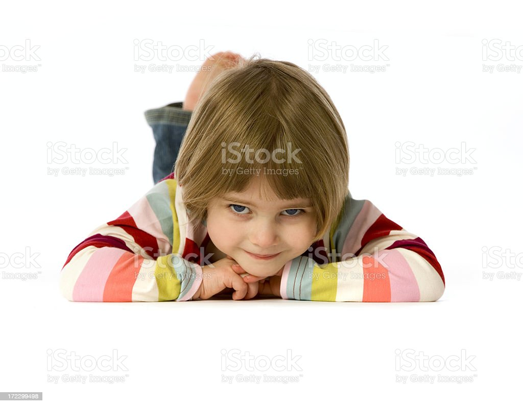 Small girl lying on her front with cheeky smile royalty-free stock photo