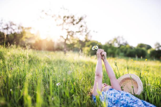 en liten flicka liggande på gräset i vår natur. kopiera utrymme. - single pampas grass bildbanksfoton och bilder