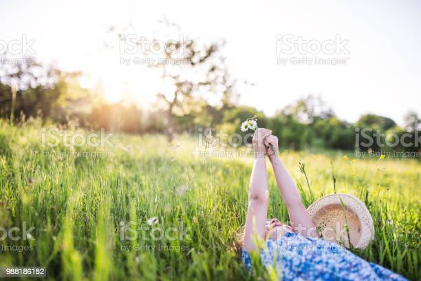 Photo of A small girl lying on the grass in spring nature. Copy space.