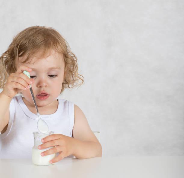 kleine mädchen von zwei jahren ist natürlicher zucker joghurt essen. - zuckerfreie lebensmittel stock-fotos und bilder