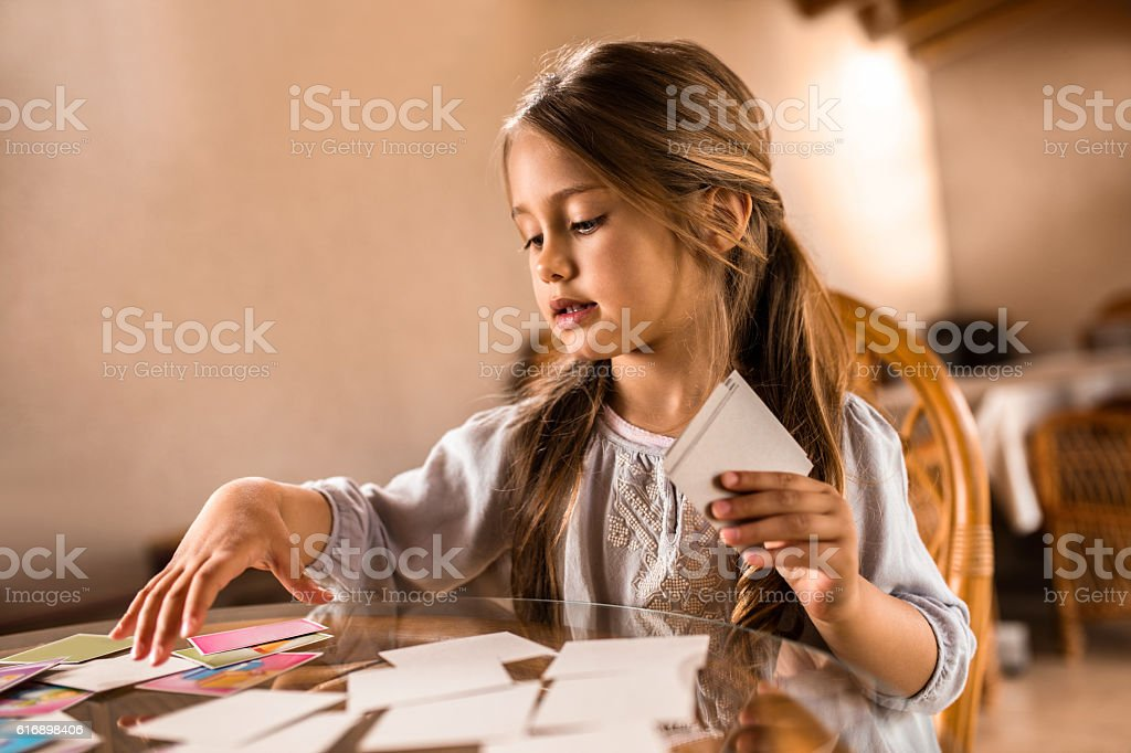 Little girl playing with cards while sitting at the table indoors.