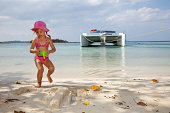 Little girl playing with her water bucket and sand on Negril beach in front of an anchored catamaran