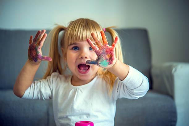 kleine mädchen spielen mit farben - lustige babybilder stock-fotos und bilder