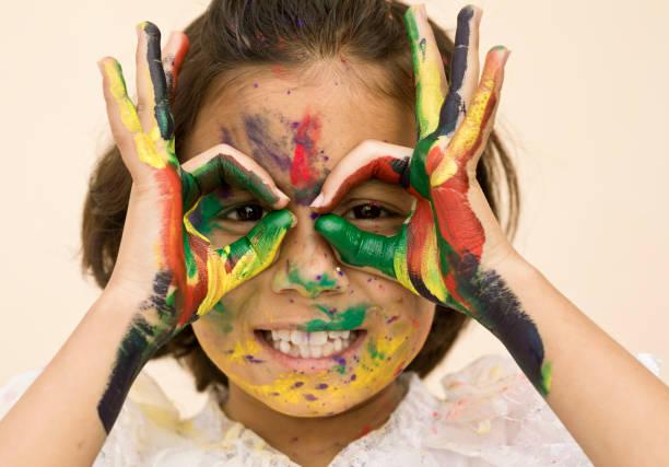 kleine mädchen spielen mit farben - indische gesichtsfarben stock-fotos und bilder