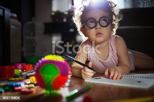 istock Small girl playing with toys on the floor 955116804
