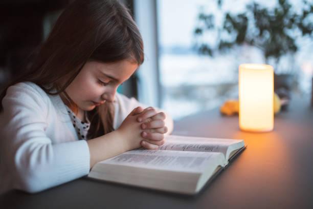 一個小女孩在家裡祈禱。 - prayer 個照片及圖片檔