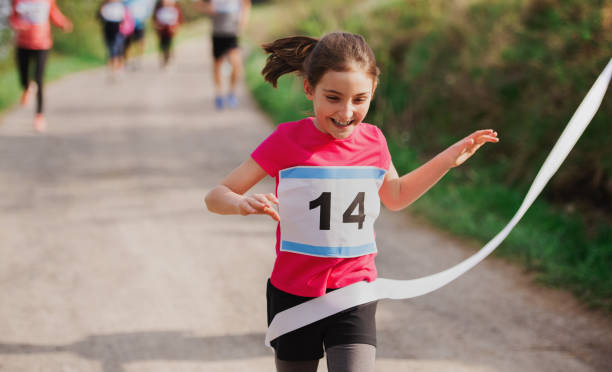 Small girl runner crossing finish line in a race competition in nature. stock photo