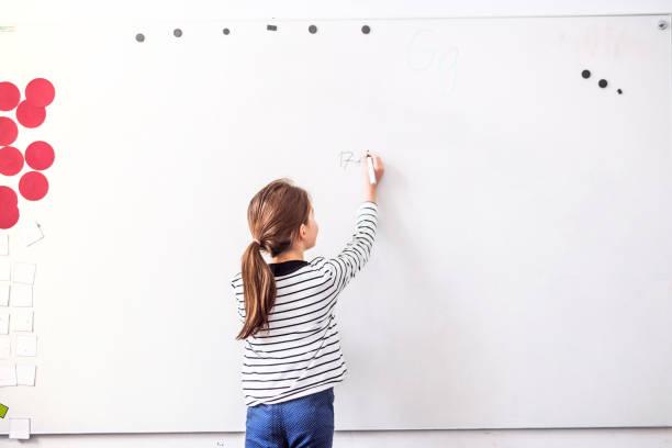 una niña de pie en la escritura de la pizarra. - pizarra blanca fotografías e imágenes de stock