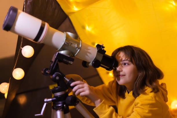 Kleines Mädchen mit Teleskop zu Hause Wohnzimmer in einem Zelt. – Foto