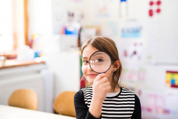 A small girl with a magnifying glass at the desk at school. stock photo