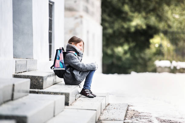 a small girl with a schoolbag sitting on the stairs in front of school. - slovacchia foto e immagini stock