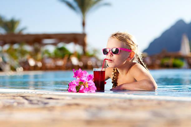 Kleines Mädchen mit cocktail im pool – Foto