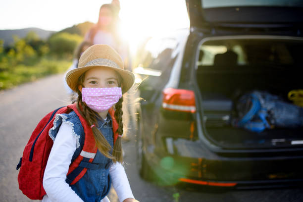 Small girl with family on trip outdoors in nature, wearing face masks. stock photo