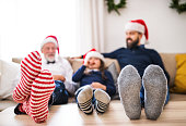 A small girl with father and grandfather sitting on a sofa at Christmas time.