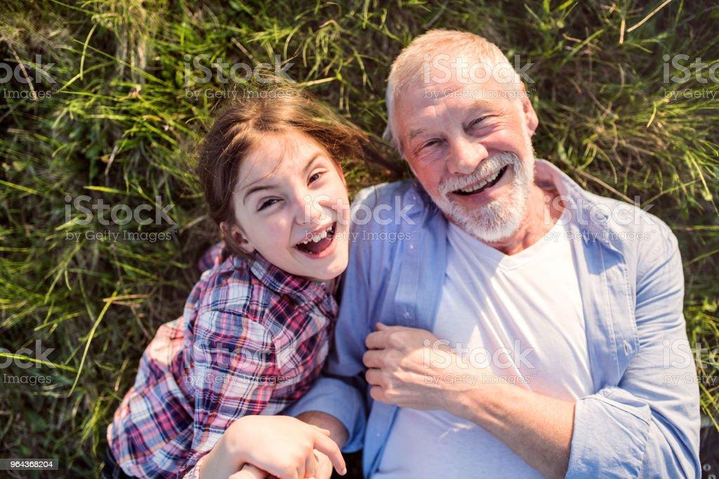 Een klein meisje met grootvader buiten in de natuur van de lente, ontspannen op het gras. - Royalty-free Bejaard Stockfoto