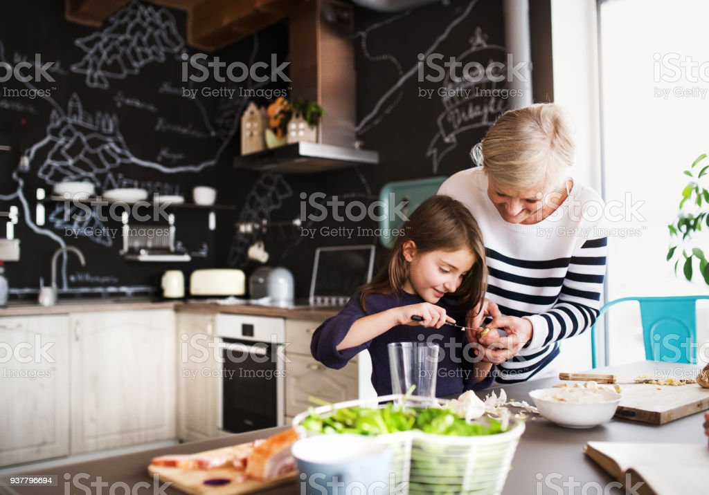 A small girl with grandmother cooking at home. royalty-free stock photo